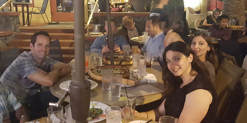 Three people sitting at outdoor dinner table, smiling at camera