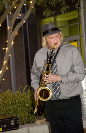 Man with long blond hair wearing hat and playing saxophone