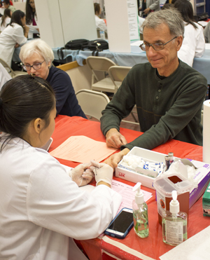 PharmD student talks to patient during El Rio Health Fair