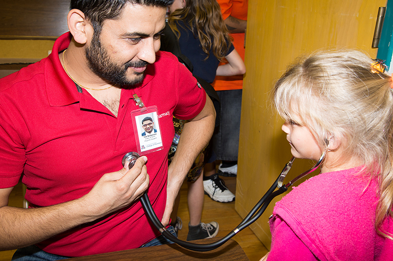 Man with dark hair pressing a stethoscope against his chest so blonde child can hear his heartbeat